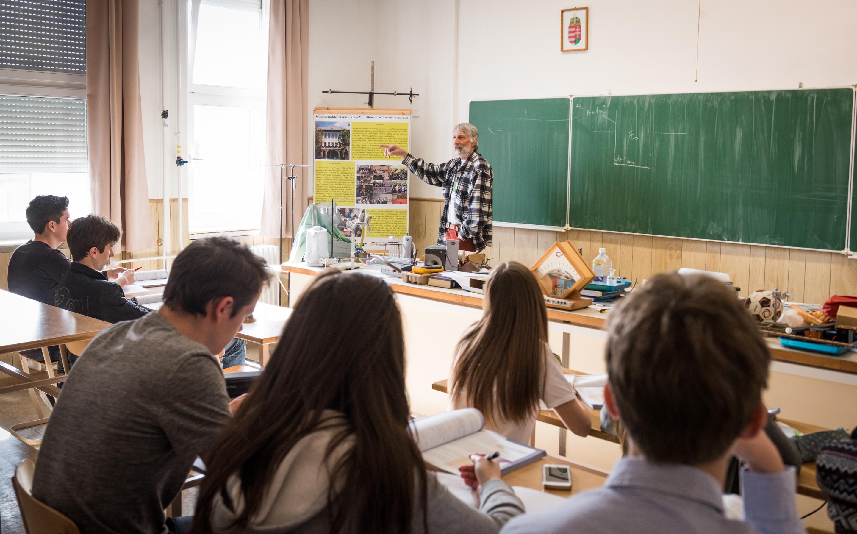 """19595efd70aa Horváth tanár úr bemegy a tanterembe, hogy megtartsa a következő óráját.  Lelkes magyarázata kihallatszik a folyosóra. """"A feszültség csökken, a  töltés ..."""